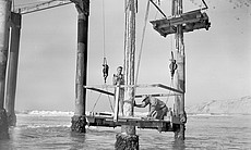 Two men work during the construction of the Scr...