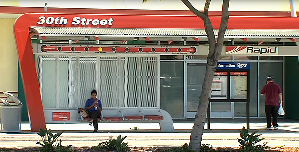 A woman sits at an MTS bus stop at 30th St. and El Cajon ...