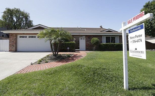 """A home for sale sits behind a sign that reads, """"sale pending,""""in San Diego, A..."""