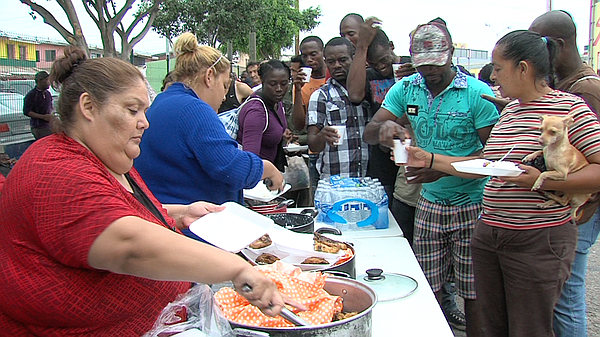 Haitian and African migrants line up for fried chicken, r...
