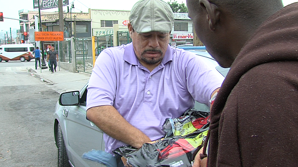 A Mexican man hands out power drinks to Haitian and Afric...