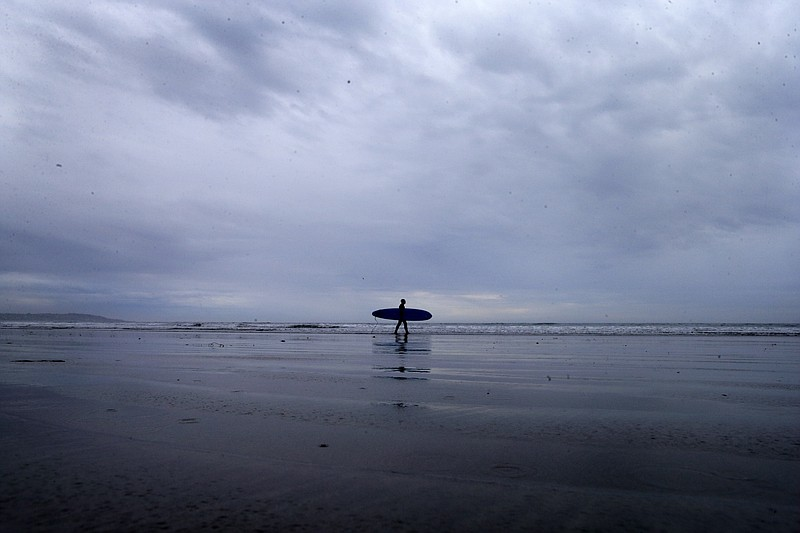 A lone surfer makes his way into the water as storm clouds come ashore in San...