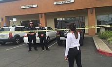 Police officers stand at the scene of an office...