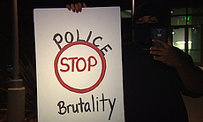 """A man holds a sign that reads """"stop police brut..."""