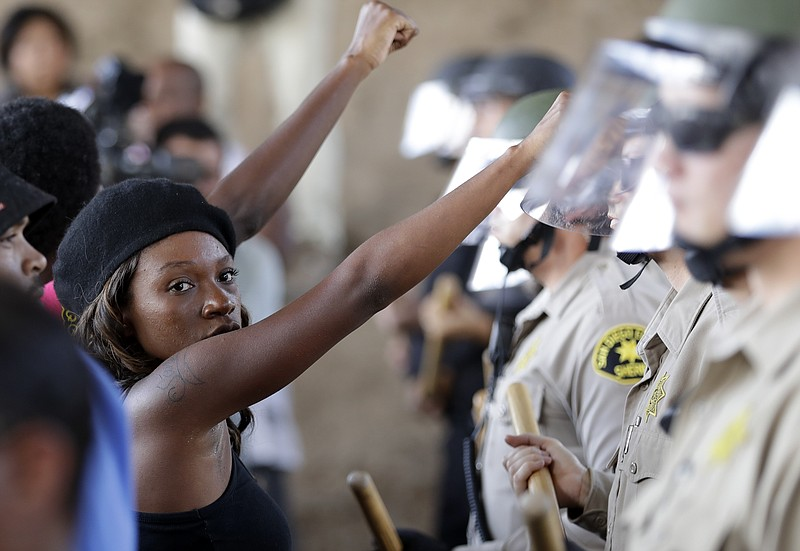 "A woman raises her fist in front of a line of police during a protest in El Cajon. Dozens of demonstrators protested the killing of a black man shot by an officer after authorities said the man pulled an object from a pocket, pointed it and assumed a ""shooting stance."" Sept. 28, 2016."