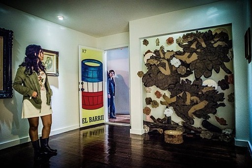 A woman looks at artwork in an apartment-turned...