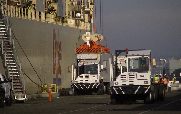 Trucks unload a ship carrying Dole fruit to the 10th Aven...