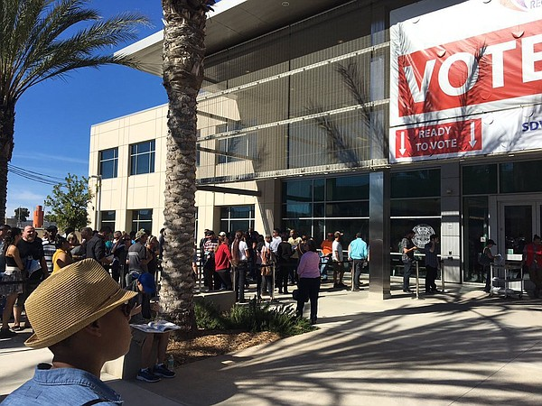 People wait in line to vote at the San Diego County regis...