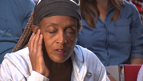 Janet Bolden, who is blind and homeless, puts her hand to...