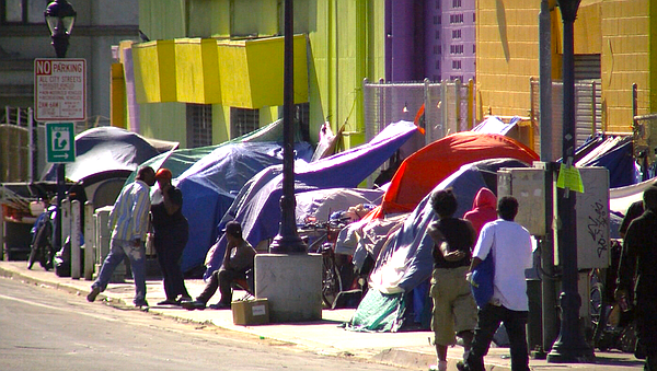 People stand outside of tents on 17th Street in San Diego...
