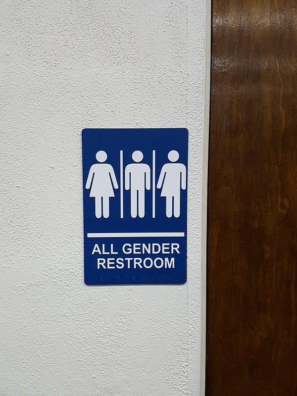 A gender neutral bathroom sign hangs in the University He...