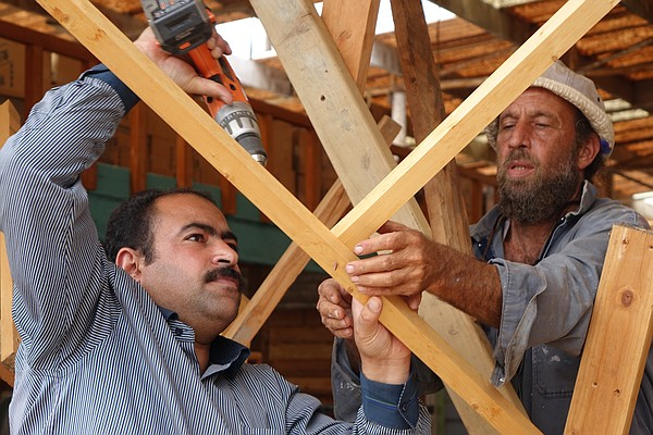 Refugee artist-in-residence Abdullah Taysan, left, uses a drill to fasten tog...