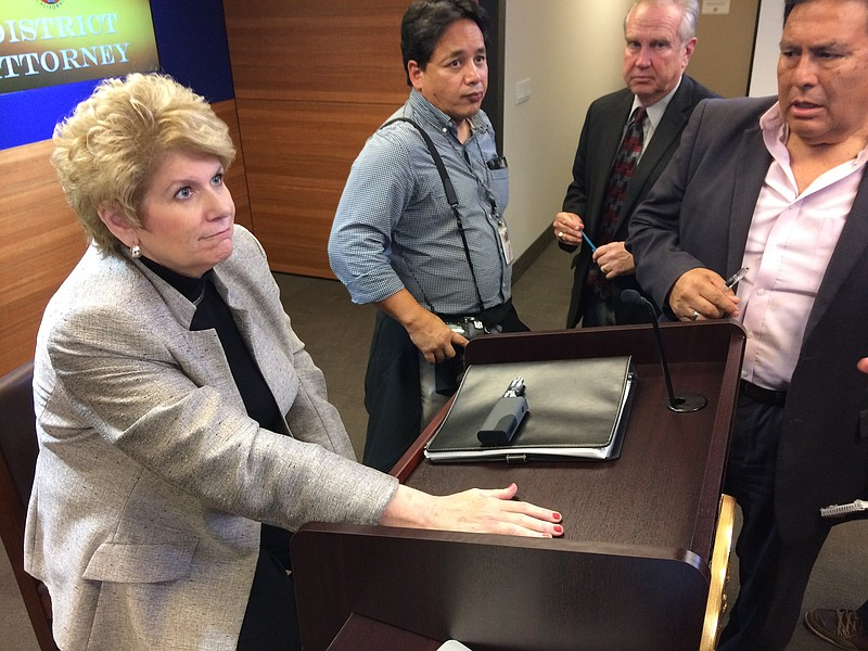 San Diego County District Attorney Bonnie Dumanis sits beside a podium as rep...