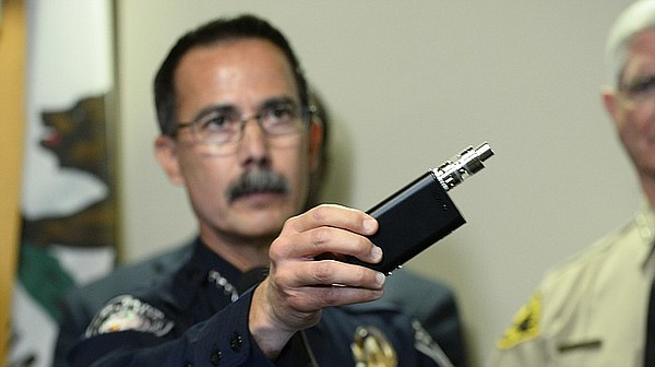 El Cajon Police Capt. Jeff Davis holds a vaping device similar to the one tha...
