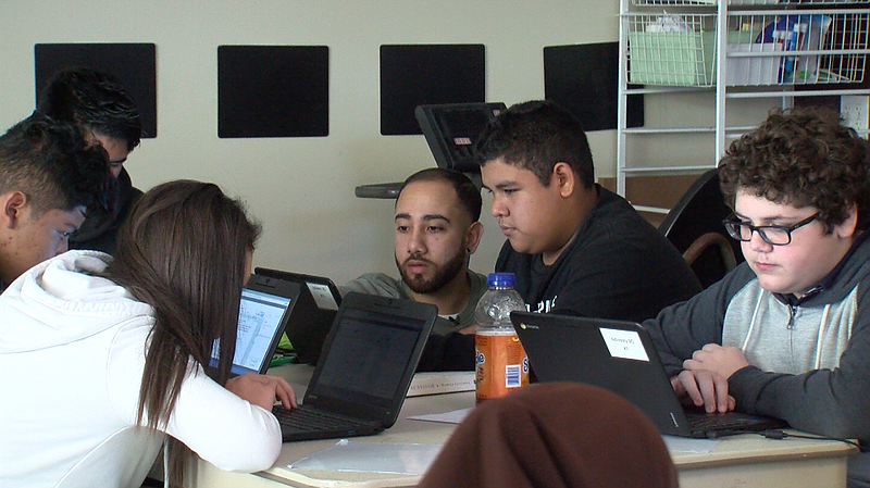 Elijah Gonzalez, Center, Helps A Student At Thrive Public School In Rolando  D.