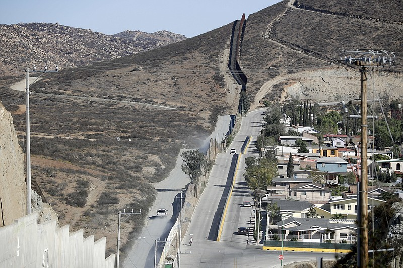A Border Patrol vehicle drives by the border fence in Tecate, Calif., left, a...