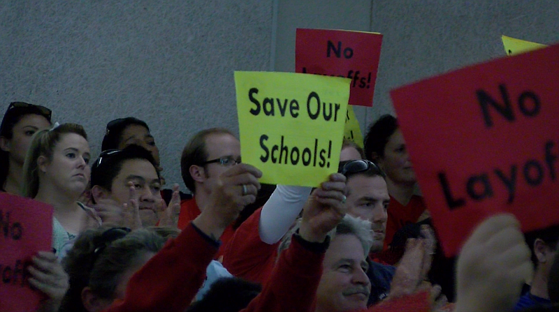 Parents and educators hold signs reading,