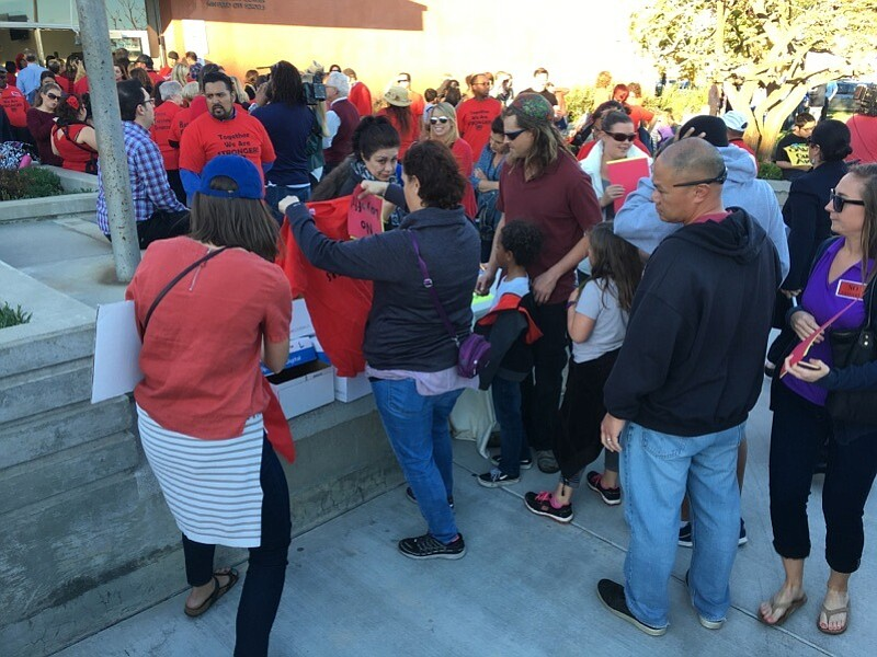 Parents and educators grab t-shirts and signs before heading into a San Diego...