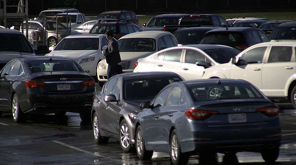 A man walks through a large employee parking lot at an office park in Kearny ...