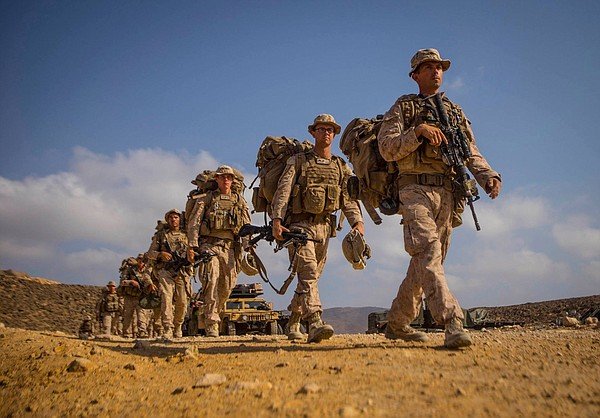 U.S. Service members with the 11th Marine Expeditionary Unit walk from their ...