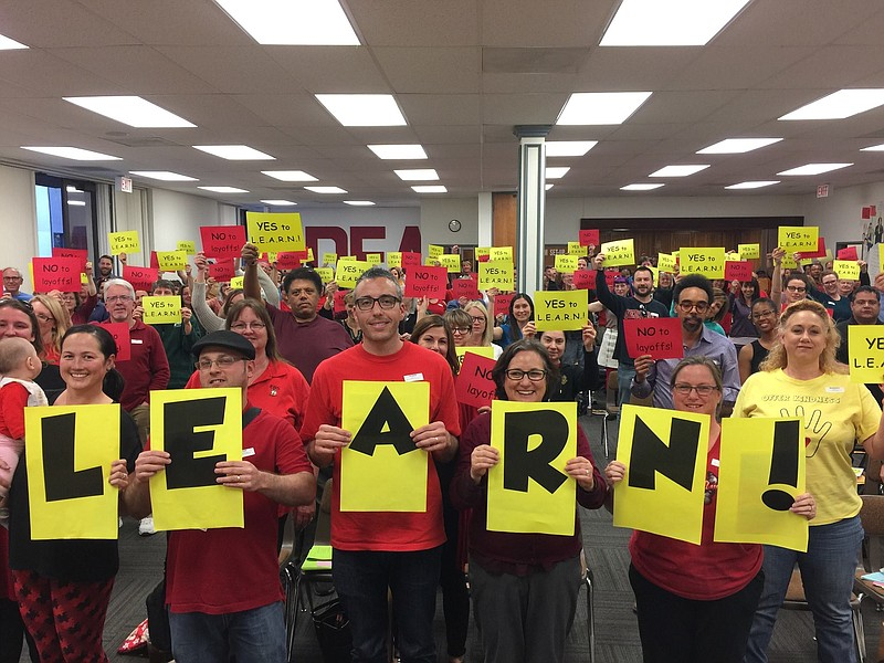 San Diego Education Association members hold up signs in support of a new uni...
