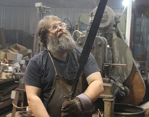 Blacksmith Ric Furrer in his workshop holding his crucibl...