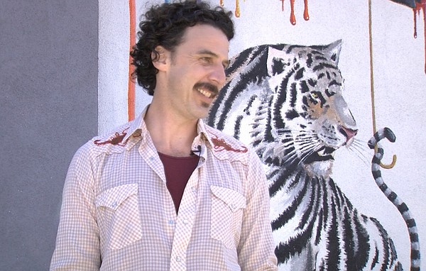 Michael Summers stands next to his tiger mural in Carlsba...