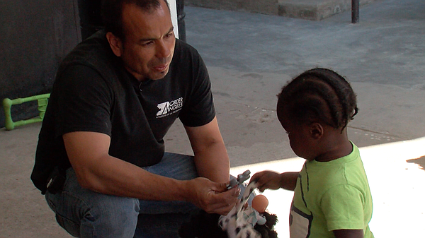 Hugo Castro, volunteer coordinator at Border Angels, plays with a Haitian chi...