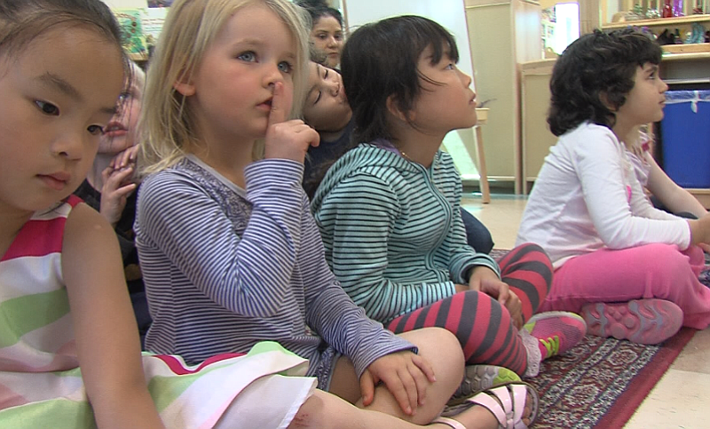 A child at the Mesa Child Development Center puts her finger to her lips as p...