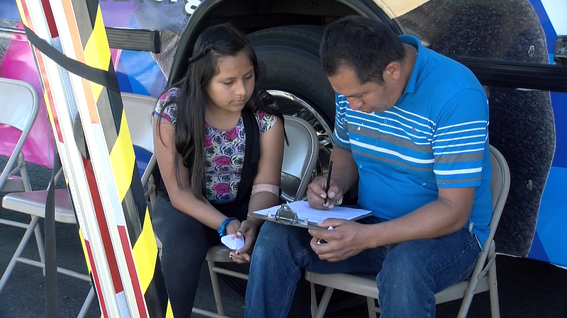 David Sanchez fills out paperwork after his 10-year-old daughter, Lizbeth, ha...