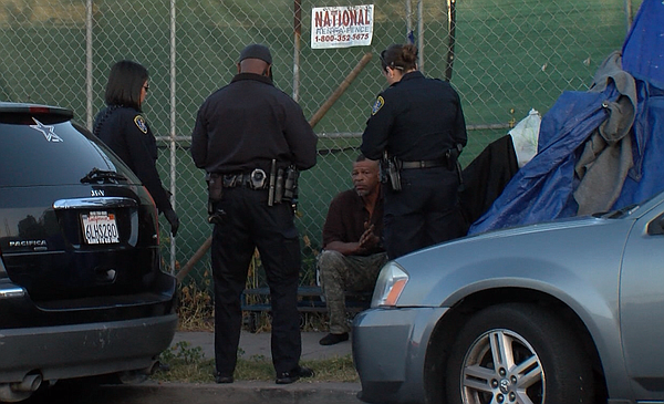 San Diego Police officers talk to a man sitting beside hi...