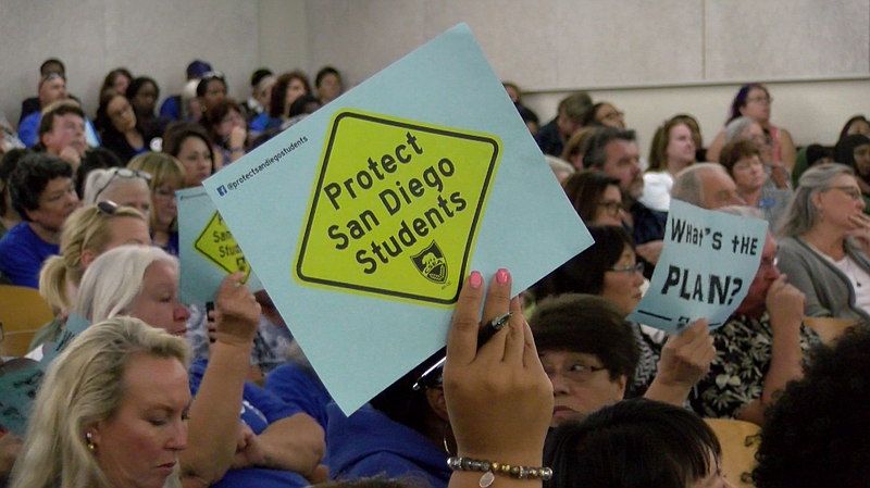 Educators hold signs that read