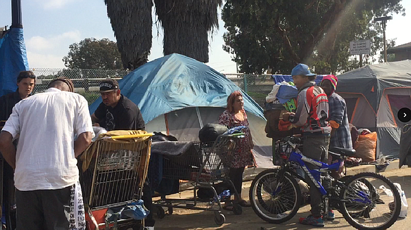 People stand near homeless encampments on 17th Street in San Diego's East Vil...