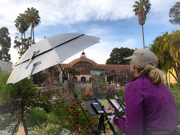 Artist paints on her canvas in Balboa Park, April 27, 2017.