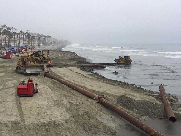 Bulldozers lay pipe and spread sand south of Oceanside pi...
