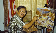 Tom Hom paints on a canvas in this undated phot...