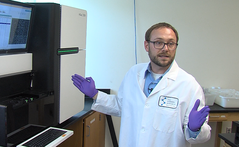 Nathan Grubaugh stands next to a gene sequencing machine at the Scripps Resea...