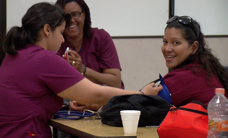 Students practice checking one another's blood pressure in a career-technical...