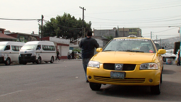 A pedestrian passes a lone yellow cab in Tijuana, July 20, 2017.