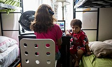Daliya Ali's daughter and son sit at a desk in ... (104900)