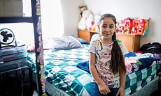 Mahmoud Alibrahim's daughter sits on a bed in t...