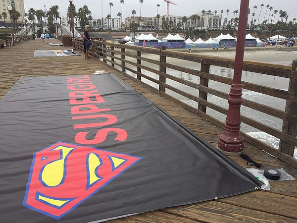 Banners being prepared on the Oceanside pier for the 10th Supergirl Pro Surfi...