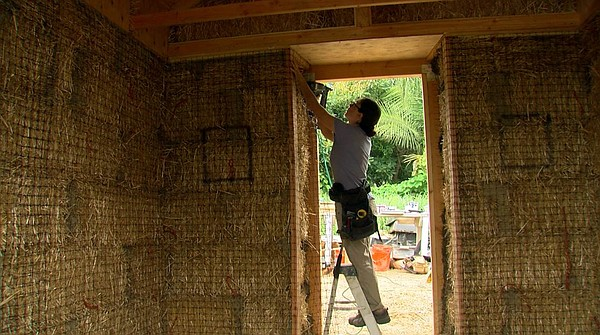A worker does construction on a straw bale greenhouse in Encinitas, July 29, ...