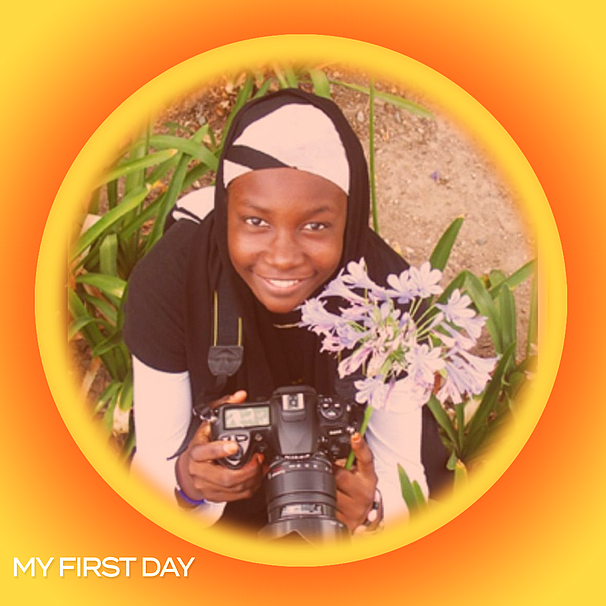 Famo Musa with her camera next to flowers. Musa is studying photography with ...