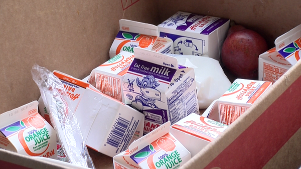 Discarded milk, orange juice and fruit fill a box at Cast...