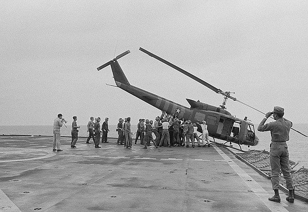 U.S. Navy personnel push a helicopter into the sea to mak...