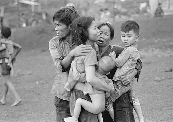 Civilians huddle together after an attack by South Vietnamese forces. Dong Xo...