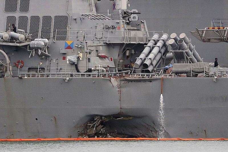 The damaged port aft hull of the USS John S. McCain, is visible while docked ...