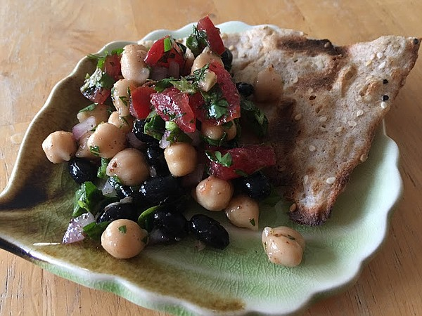 Balela salad in a dish with a piece of sangak bread in an...