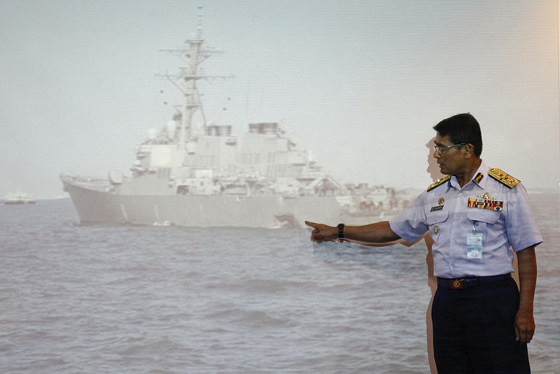Malaysian Maritime Director Indera Abu Bakar points the damage of USS John S....